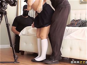 student Noelle Easton teased by two hooded folks